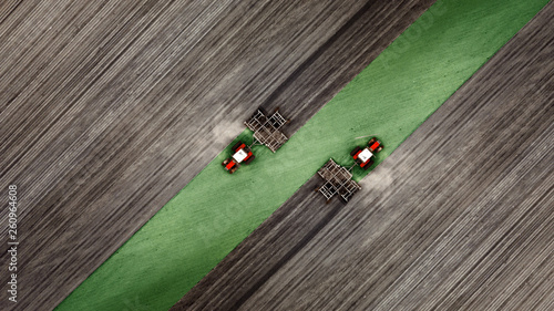 Fotografia Aerial top view of a tractor, combine harvester plowing agricultural land in the