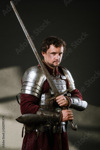 Obraz na plátne Medieval man knight in armor and weapon on dark background