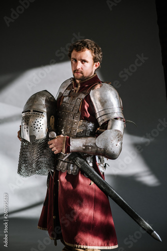 Fototapeta Medieval man knight in armor and weapon on dark background