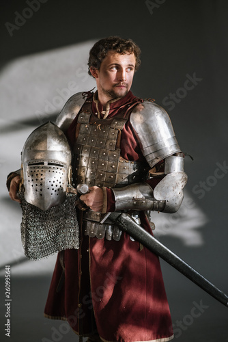 Photo Medieval man knight in armor and weapon on dark background