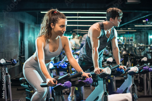 Obraz na plátně Attractive young sporty woman and handsome muscular man doing spinning on cyclin