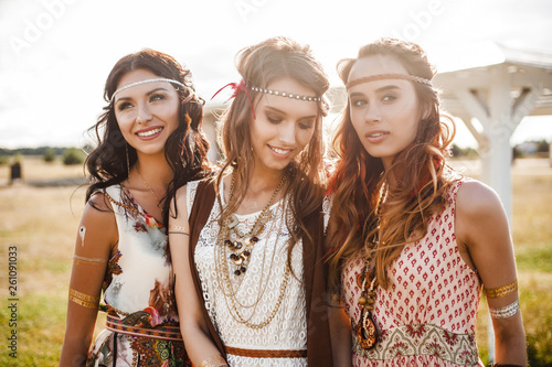 Obraz na plátně Three cute beautiful hippie girl in the setting sun, outdoors, the best of frien