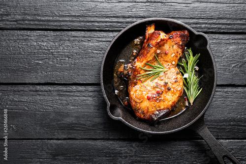Fotografia Fried pork steak in frying pan on black wooden background.