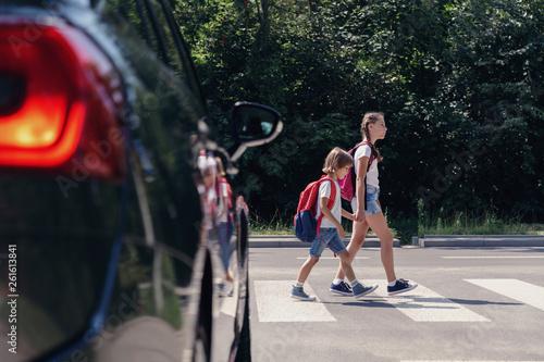 Fotografija Children next to a car walking through pedestrian crossing to the school