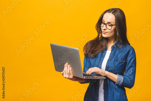 Canvas Print Young happy smiling woman in casual clothes holding laptop and sending email to her best friend