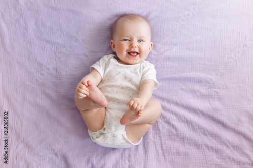Portrait of cute adorable smiling laughing white Caucasian baby girl boy with blue eyes four months old lying on bed looking at camera Fototapeta