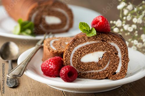 Valokuvatapetti Delicious chocolate roll sponge cake with vanilla cream and mint leaves