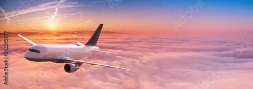 Canvas-taulu Commercial airplane jetliner flying above dramatic clouds.
