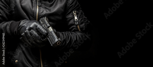 Canvas-taulu a man in a black jacket and black gloves holding a gun on a dark back