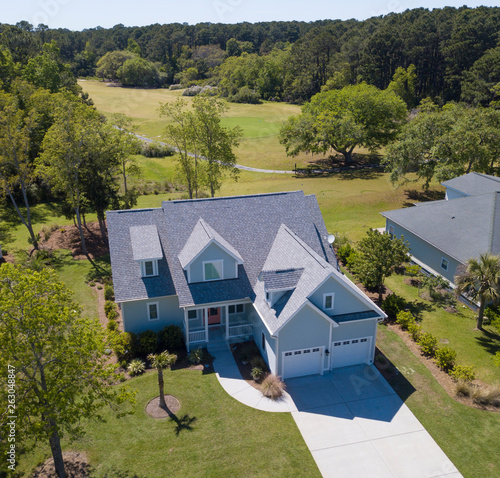Fotografia Low aerial view of house with new roof and golf course behind.