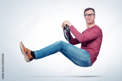 Fotografia Surprised man in casual wear and glasses drives a car with a steering wheel