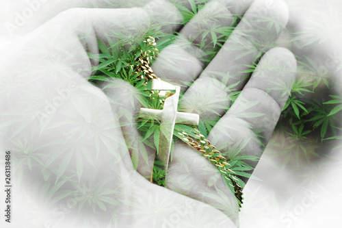Tablou Canvas Alternative Lifestyle Concept with Gold Cross In Hand With Marijuana Leaves High