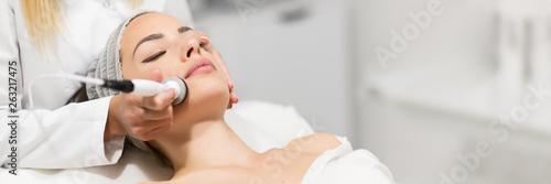 Tableau sur Toile Beautiful woman in professional beauty salon during photo rejuvenation procedure