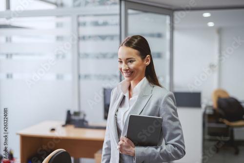Fototapeta Beautiful Caucasian brunette in formal wear standing in office with tablet in hands