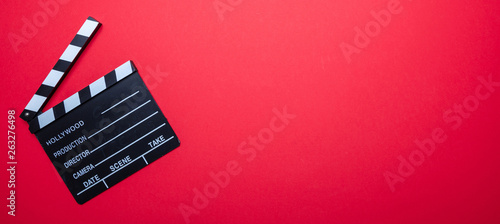 Fotografiet Movie clapperboard on red color background, banner, top view
