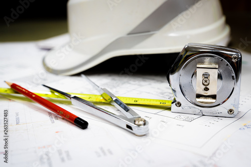 Canvas Print White safety helmet and drawing tools on naval architects working desk