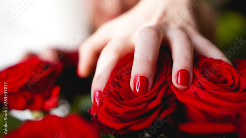 Photo Woman hands with manicure red nails closeup and rose