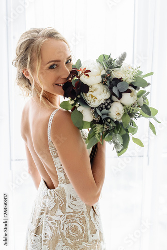Fotografia Very beautiful and happy bride holds her wedding bouquet of different blooming f