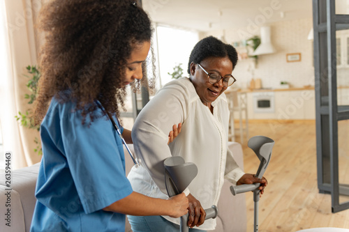 Fényképezés Curly young nurse giving crutches to aged woman after leg surgery