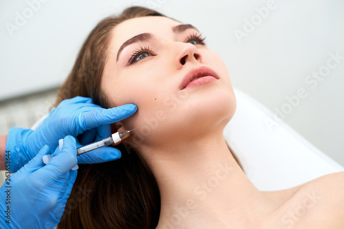 Fotografija Beautician doctor with filler syringe making injection to jowls