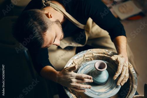 Potter modeling ceramic pot from clay on a potter's wheel Fototapet