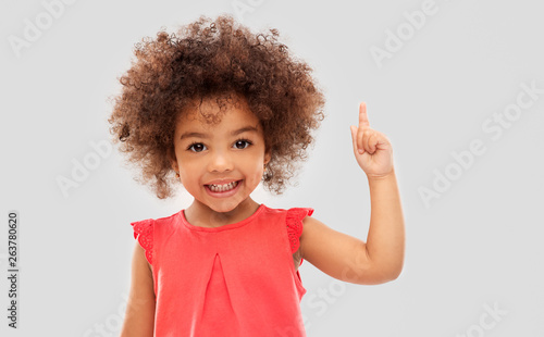 Obraz na plátne idea, warning and childhood concept - happy little african american girl pointin