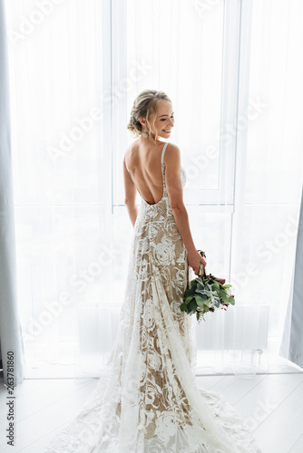 Murais de parede Awesome bride in a long wedding dress with a beautiful bouquet in hand and with
