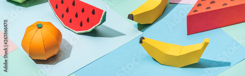 panoramic shot of handmade cardboard fruits on multicolored paper