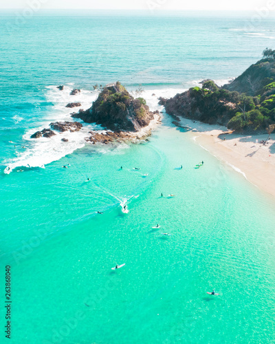Fotografia Aerial shot at sunrise over the ocean and white sand beach with swimmers and sur