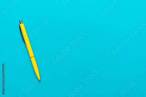 Foto photo of yellow ballpoint pen over turquoise blue background with copy space