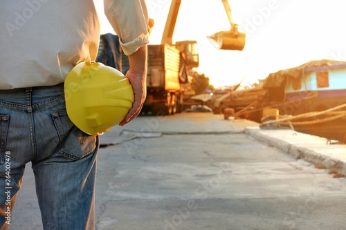 Slika na platnu Back side of foreman holding yellow helmet and looking at backhoe excavator work