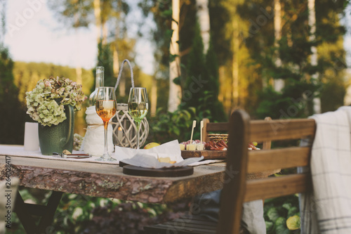 Foto summer garden table decorated with flowers and candles, evening party with wine,