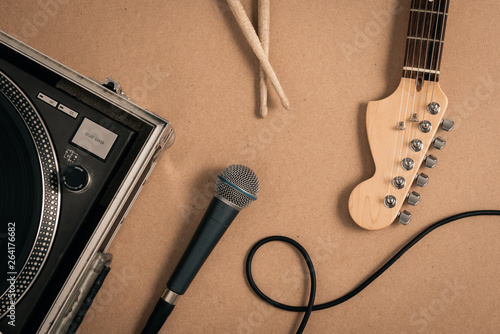 Photo View from above of a record player, an electric guitar headstock, a microphone a