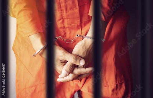Billede på lærred a prisoner hands in handcuffs behind the bars of a prison in orange jumpsuit clo