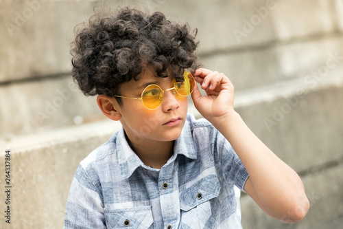 Fotografija Young curly headed boy with trendy yellow shades