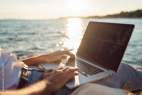Stampa su Tela Senior man working on his laptop lying on deck chair on the beach during sunset