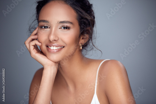 pretty girl smiling into the camera, beautiful woman with smile, happy girl on grey background leaning on her arm, nice girl laughing