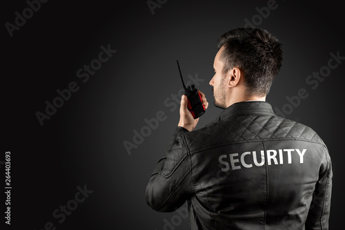 Photo The man, security, is holding a walkie-talkie