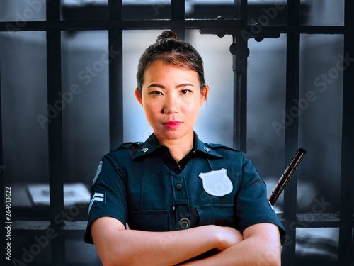 Obraz na płótnie young serious and attractive Asian Chinese guard woman standing on cell at State