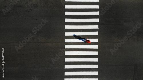 Foto One pedestrian crossing zebra crosswalk, aerial, top view