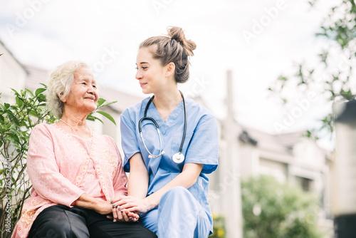 Obraz na plátně caregiver holding hand of happy elderly woman