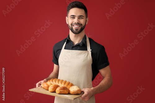 Tableau sur Toile Baker with fresh bread on color background