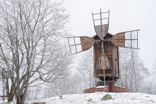 Winter landscape with old and abandoned windmill at daytime in Finland