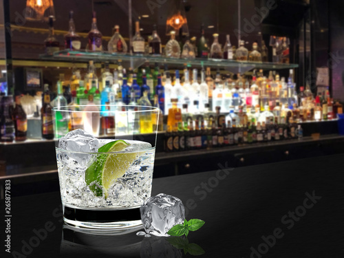 Fotografie, Obraz A glass of gin tonic or vodka lime with ice on bar counter and blurry bottles ba