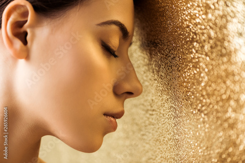 Canvas Print young beautiful woman with closed eyes and shiny makeup on golden textured backg