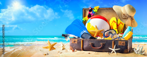 Beach accessories in suitcase on sand. Family holidays concept
