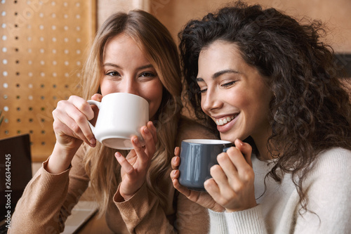 Canvas Print Happy girls friends sitting in cafe talking with each other drinking tea or coffee