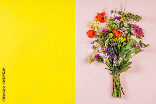 Wild flower bouquet on pink and yellow background Fototapeta