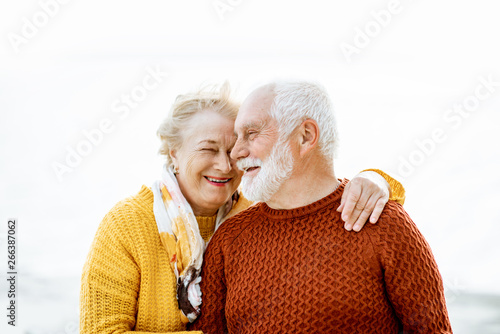 Portrait of a happy senior couple dressed in colorful sweaters hugging on the sandy beach, enjoying free time during retirement near the sea #266387062