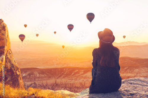 Fotografia A woman alone unplugged sits on top of a mountain and admires the flight of hot air balloons in Cappadocia in Turkey
